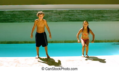 Siblings jumping together in the swimming pool