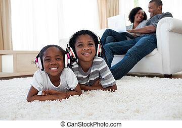 Siblings listening music lying on the floor