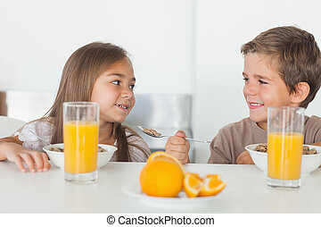 Siblings looking at each other during breakfast