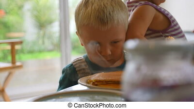 Siblings looking at pancakes on dining table 4k - Front view...