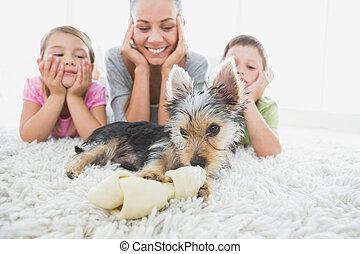 Siblings lying on rug looking at their yorkshire terrier ...