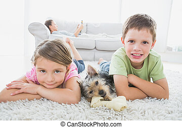 Siblings lying on rug with yorkshire terrier smiling at...