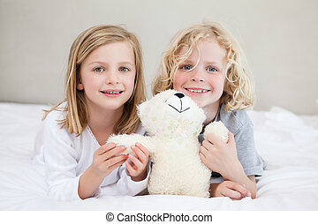 Siblings lying on the bed with teddy