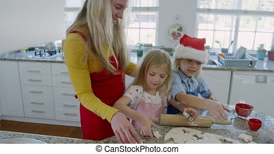 Siblings making christmas cookies at home