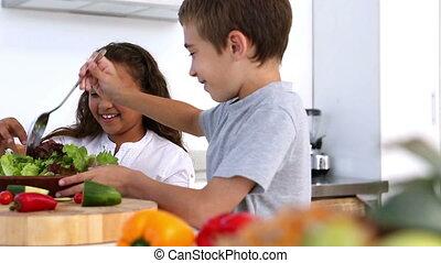 Siblings making salad together