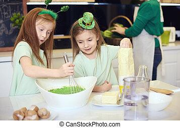 Siblings mixing green fondant icing