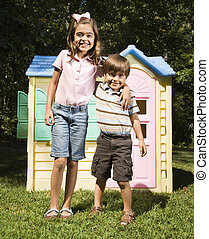 Hispanic boy and girl in front of outdoor playhouse smiling at viewer.