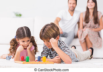 Siblings playing board game on the floor