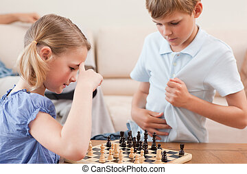Siblings playing chess in a living room