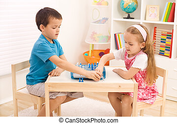 Siblings playing chess in the kid's room