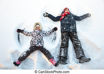 Siblings playing in a snow enjoying winter