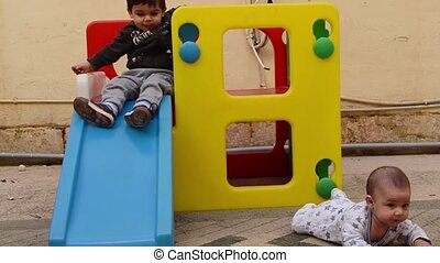 siblings playing in the backyard, toddler sliding down from plastic play house while his baby brother is having tummy time on the carpet