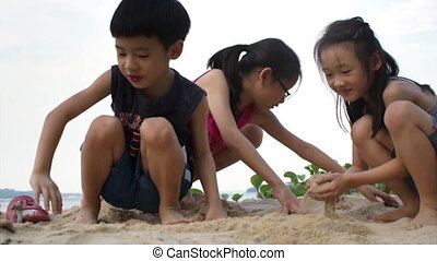 Siblings playing on the beach trying to build Sand Castle.