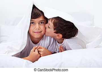 Siblings playing under the quilt
