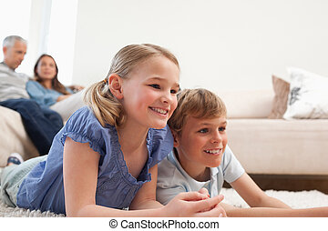Siblings playing video games while their parents are watching