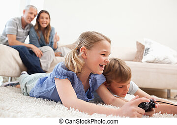 Siblings playing video games with their parents on the background in a living room