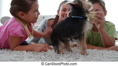 Siblings playing with puppy and bone with their mother at...