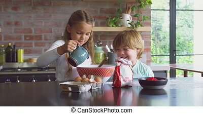 Siblings preparing cookie on worktop in kitchen at comfortable home 4k