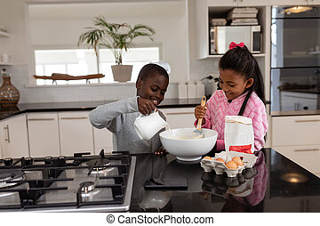 Siblings preparing food on a dining table in kitchen at home...