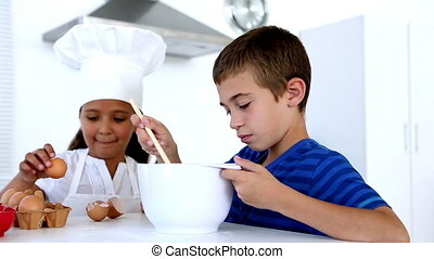Siblings preparing pastry together at home in kitchen