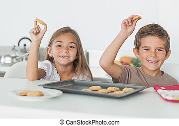 Siblings raising homemade cookies