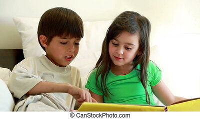 Siblings reading a book together