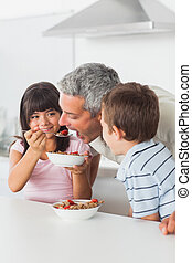 Siblings sharing cereal with their father