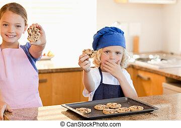 Siblings showing their cookies
