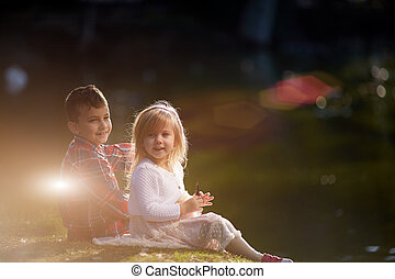 Siblings, sister, brother hugs . Two children, older and younger sitting on the shore of the lake