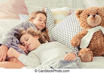 Siblings sleeping in bed