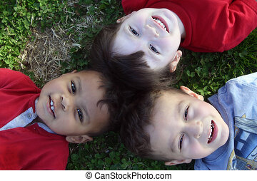 Adorable kids smiling. I took this picture of my kids on the grass looking into the sky.