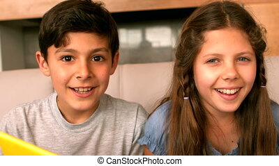 Siblings smiling at camera on couch in slow motion