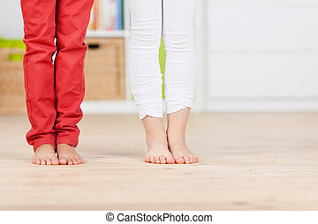 Siblings Standing On Hardwood Floor