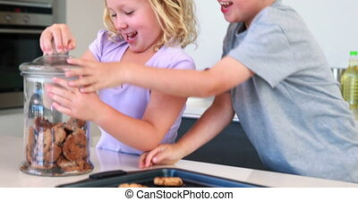 Siblings taking cookies from the jar and eating them at home...