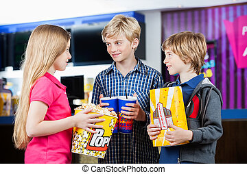 Siblings Talking While Holding Snacks At Cinema