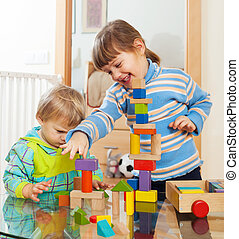 siblings together playing with  toys