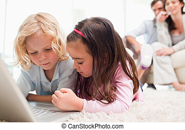 Siblings using a notebook while their parents are in the...