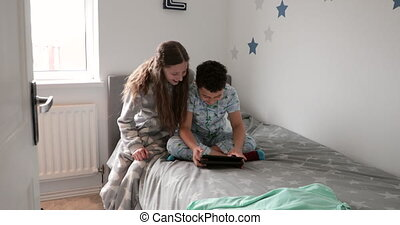 Siblings Using Digital Tablet - Little boy is sitting on his...