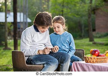 Siblings Using Smartphone At Campsite