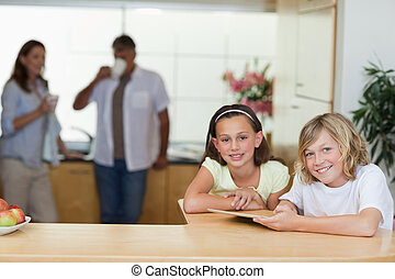 Siblings using tablet in the kitchen with parents behind them