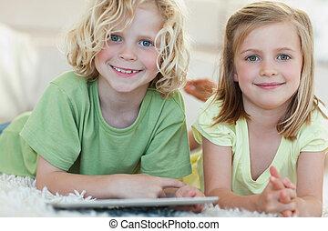 Siblings using tablet on the floor