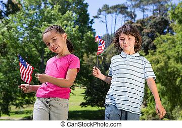 Siblings waving american flag