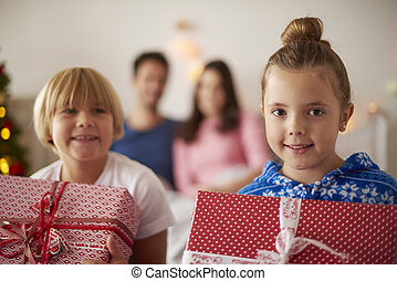 Siblings with Christmas presents in bedroom