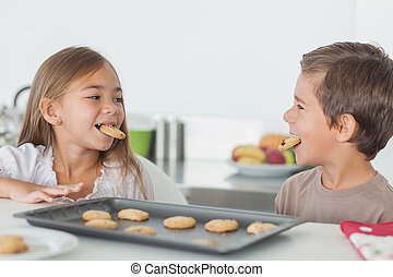 Siblings with cookies in their mouth