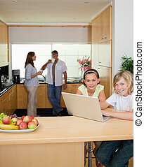 Siblings with laptop in the kitchen with parents behind them