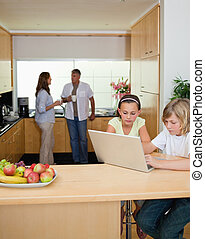 Siblings with notebook in the kitchen and parents behind them