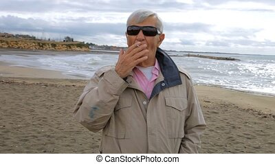 Mature man smoking cigarette on beach