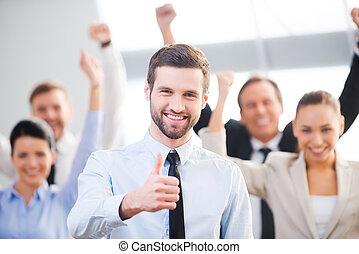 sicher, gefühl, geschäftsmann, auf, glücklich, hintergrund, daumen, team., ausstellung, lächelndes stehen, seine, kollegen, während