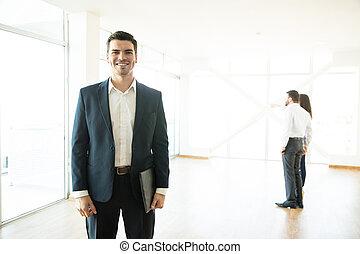 sicher, immobilienmakler, lächeln, mit, klienten, in, hintergrund, an, neues heim