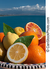 Sicilian fruits - Oranges and lemons with blue sea, Mount...